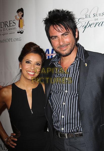 Eva Longoria, Beto Cuevas<br /> The Padres Contra El Cancer 13th annual 'El Sueno De Esperanza' Gala at Club Nokia in Los Angeles, California, USA.<br /> September 24th, 2013<br /> half length black dress hand on hip sleeveless blue stripe shirt suit jacket grey gray stubble facial hair <br /> CAP/ADM/KB<br /> &copy;Kevan Brooks/AdMedia/Capital Pictures