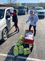 Lydia Velasco (left), an ESL aide at Greenland Elementary School, and Lori Gaither, a literacy aide, work together March 21, 2020, during a giveaway of food and household items at the school. The school, along with Lincoln, Gravette and Pea Ridge, partners with Essentials Outreach and Tyson Foods to provide necessary items to families in its district on third Saturday of the month. After serving 27 families in its first month last month, Greenland gave items to 271 individuals on Saturday. Visit nwaonline.com/200322Daily/ for today's photo gallery.<br /> (NWA Democrat-Gazette/Andy Shupe)