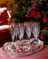 An antique silver tray with champagne flutes displaying little greeting cards tied with ribbons