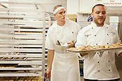 Jay Beaver, cooking with Chef Adam Rose of Il Palio, eyes a tray of pretzel bread being carried by Weathervane Sous Chef Spencer Carter in the kitchen, which is shared by both teams during the competition.