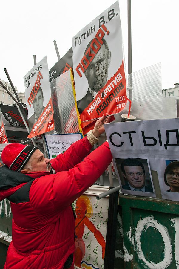 "Moscow, Russia, 13/01/2013..A man places a mud-spattered portrait of President Vladimir Putin in a skip marked ""for garbage"". Thousands of opposition protesters carried posters of President Vladimir Putin and members of the Russian parliament with the word ?Shame? written in red at a protest called the March Against The Scoundrels. The protest was against the new law banning the adoption of Russian children by Americans, widely seen as a response to the recently passed USA Magnitsky Act."