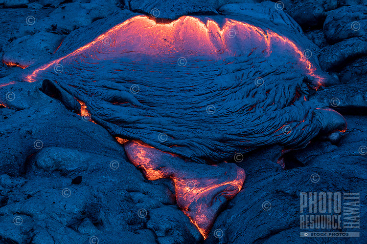 On a very rainy day, dawn casts a blue light over cooling pahoehoe (smooth, unbroken lava) on the coastal plains of Pulama Pali, Puna, Hawai'i Island; a section of molten lava looks like the outline of a manta ray, September 2017.