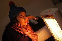 Ragazza si scalda con stufetta elettrica a causa della crisi energetica..Girl heats with electric stove because of the energy crisis....