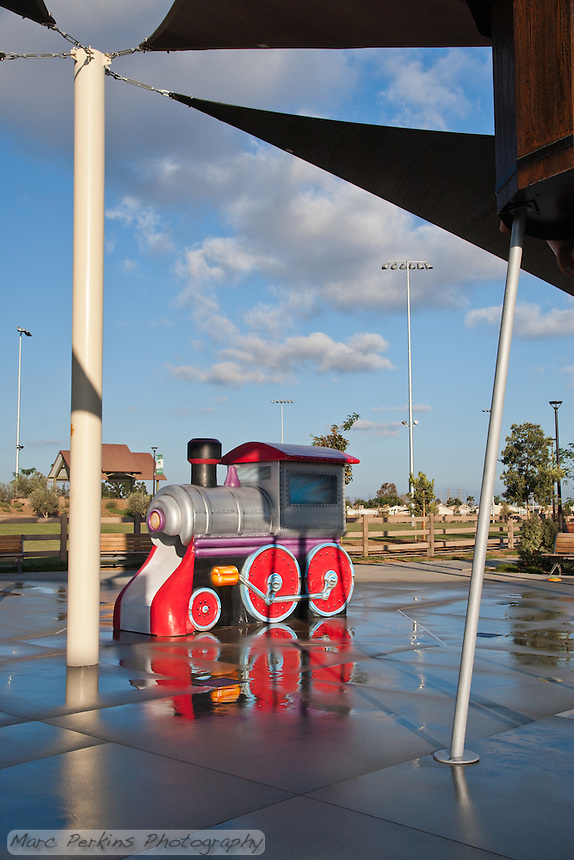 The train at the splash pad of Stanton Central Park.  Water creates lovely reflections of the cloudy sky and train; the water tower frames the train in the upper right (it can be cropped out to make this just an image of the train).  The bandstand can be seen in the distance.