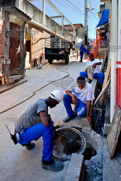 Workers examine the drainage system during the construction of an access road, all part of the Morar Carioca urbanising project, in the Morro da Babilonia favela.