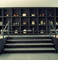 In the dining area an entire wall behind the table is taken up with a collection of ceramics displayed on modular square open shelves