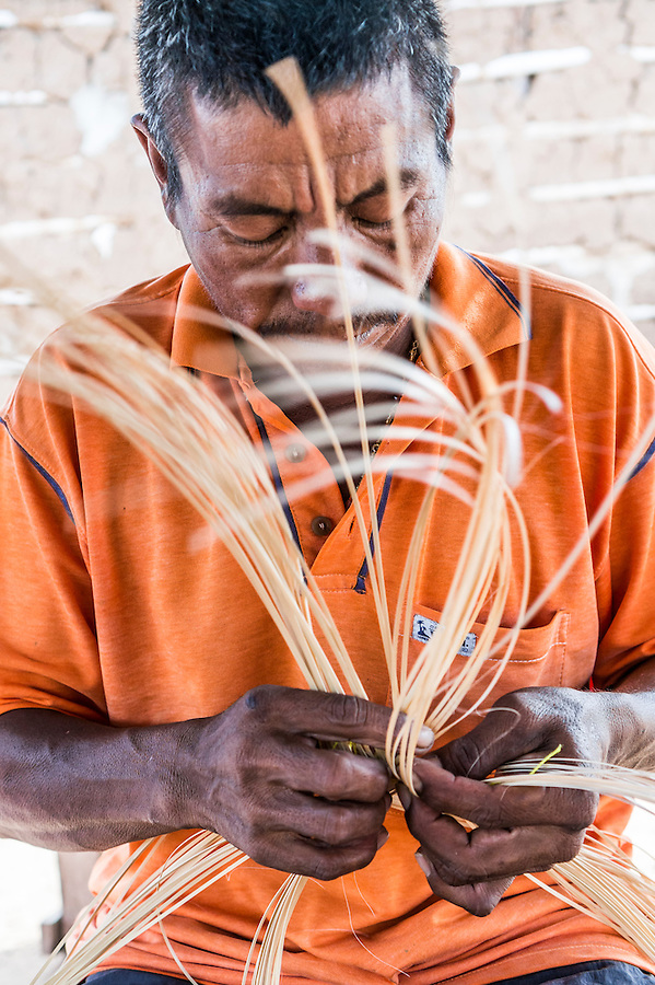 Wayuu indigenous man constructing a bamboo hat in the regional style of La Guajira, Colombia.  Weaving is mostly a female profession in Wayuu communities, but some men also weave hats and textiles.
