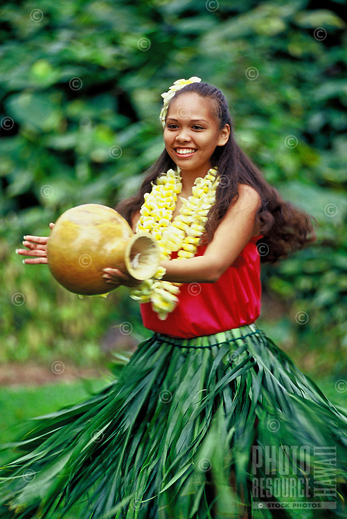 Young hula dancer with leis ipu (gourd) and ti leaf skirt