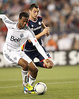 Vancouver Whitecaps FC defender Carlyle Mitchell (19) works to clear ball as New England Revolution forward Blake Brettschneider (23) defends. In a Major League Soccer (MLS) match, the New England Revolution defeated Vancouver Whitecaps FC, 4-1, at Gillette Stadium on May 12, 2012.