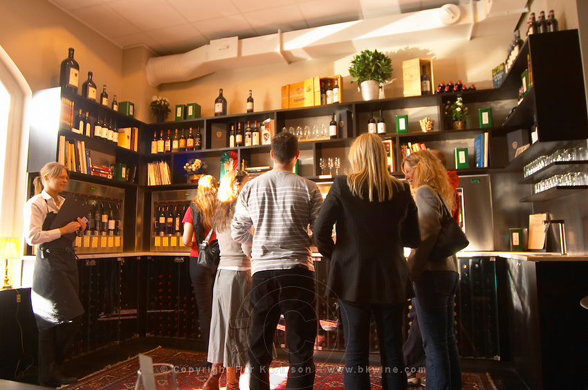 The interior of the wine bar Terrenos Vinotek. A group of people gathered around the machines that dispenses the doses of wine in a self service fashion.  Stockholm, Sweden, Sverige, Europe