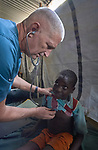 Dr. Clarke McIntosh, a pediatric pulmonologist from South Carolina in the United States, examines a young patient in the Mother of Mercy Hospital in Gidel, a village in the Nuba Mountains of Sudan. The area is controlled by the Sudan People's Liberation Movement-North, and frequently attacked by the military of Sudan. The Catholic hospital is the only referral hospital in the war-torn area.