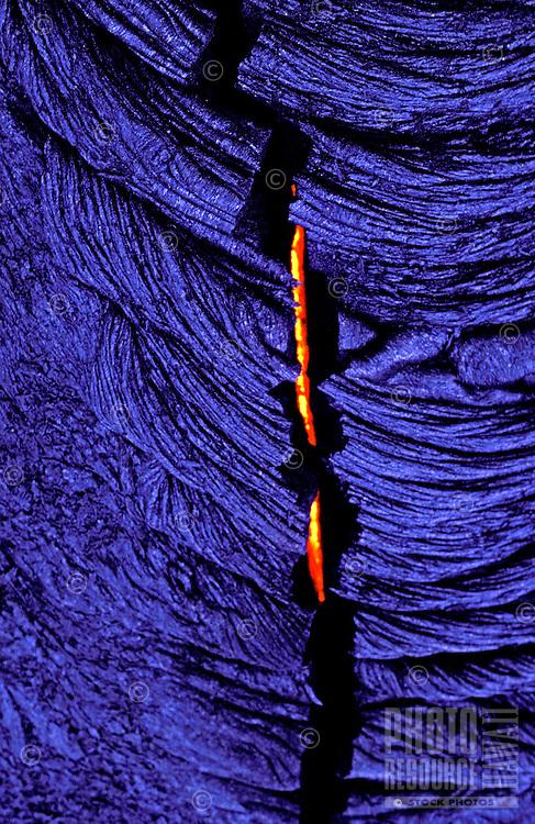 Crack in lava rock reveals fiery molten stream.