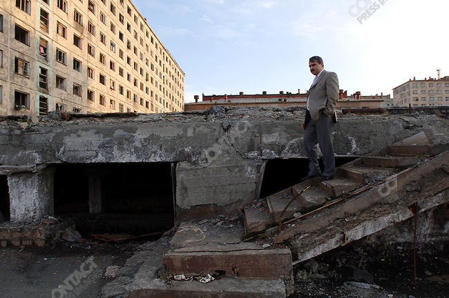 Ali G. Kerimov, a deputy of the city council, walks over the remains of an apartment building, next to another abandoned building, declared unsafe because of problems with the foundations due to a thawing permafrost, June 15, 2007
