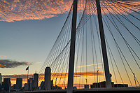 This silouett of the Dallas skyline and Margaret Hunt Hill Bridge up close in the downtown area of the city at sunrise.  The cloud over the bridge picked up the colors in the sky and along the horizon as the day was begining in this cityscape.