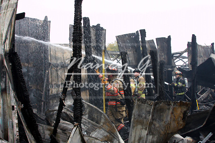 Firefighters working a scene to douse a fire in a collapsed building