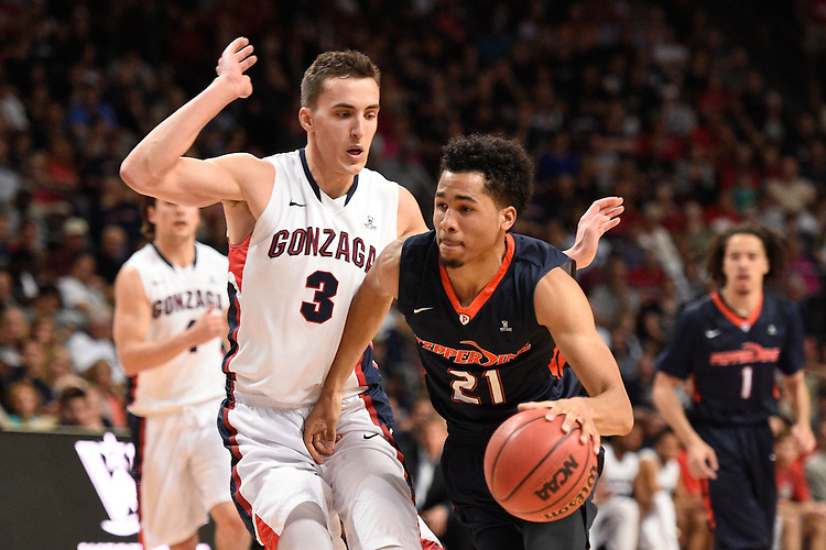 March 9, 2015; Las Vegas, NV, USA; Pepperdine Waves guard Shawn Olden (21) dribbles the basketball against Gonzaga Bulldogs guard Kyle Dranginis (3) during the second half of the WCC Basketball Championships at Orleans Arena.