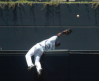 padres.1.0731.jl.jpg/photo Jamie Scott Lytle/Padres Damian Jackson climbs the center field wall is a great attempt to steal the Reds Wily Mo Pena's home run in the 2nd inning.