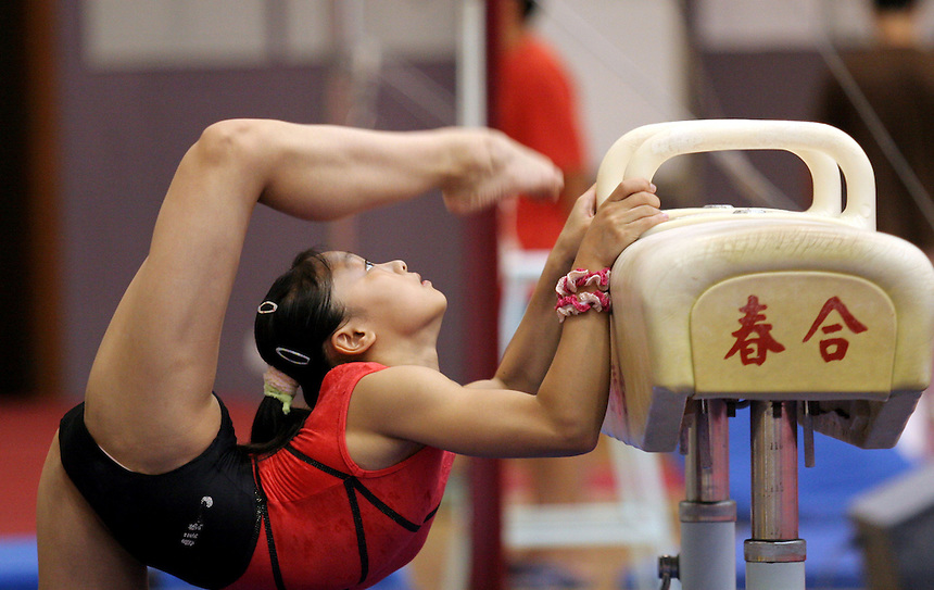 A Girl on China's national gymnastics team warms up before training in Beijing.