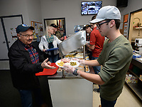 NWA Democrat-Gazette/ANDY SHUPE<br /> Riley Haile (right), a senior at Farmington High School and Boys State alumnus, serves a traditional Thanksgiving meal Wednesday, Nov. 27, 2019, to Jay Pense, a 33-year veteran of the U.S. Air Force and retired worker at the city of Fayetteville, at the Shelton Tucker Craft American Legion Post 27 in Fayetteville. Volunteers also assembled and delivered meals to homebound veterans at their homes.