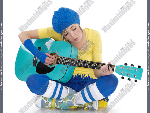 Young woman sitting on the floor and playing the guitar. Isolated on white background.