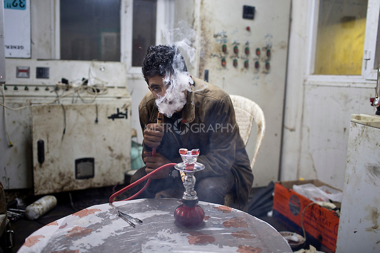 19/02/15 --TANJERO, IRAQ: Jamal (17) smokes flavored tobacco from a small hookah pipe inside the utility cabin.<br /> <br /> The family of Yezidis, displaced from Sinjar, live next to an oil refinery in the Kurdish Region of Iraq. The young men run the refinery 24 hours a day with little to no safety equipment. Reporting for this article was supported by a grant from the Pulitzer Center on Crisis Reporting