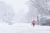 A woman out for a run in the snow in the village of Redbourn, Hertfordshire, UK. Sunday 10 December 2017.