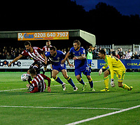 Brentford FC scramble the ball clear with AFC Wimbledon's Cody McDonald and Dean Parrett (L-R) looking to score during the Carabao Cup match between AFC Wimbledon and Brentford at the Cherry Red Records Stadium, Kingston, England on 8 August 2017. Photo by Carlton Myrie.