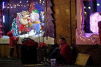 A homeless wait for tips next to a display store decorated for Christmas holidays in New York, 12/9/2015 Photo by VIEWpress