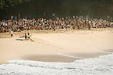 USA, Hawaii, crowd watches Ramon Navarro run up the beach after surfing a huge wave, Waimea Bay, Oahu