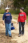 Two Caucasian senior women laugh, talk and walk carrying maps in Rowan Oak Woods of William Faulkner in Oxford, Mississippi