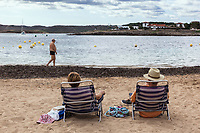 Spain. Balearic Islands. Minorca (Menorca). Na Macaret.  Mediterranean Sea. A couple of elderly persons seat on plastics chairs and enjoy resting on a sandy beach. An old man walks on the seashore. The city is part of the autonomous community of the Balearic. In Spain, an autonomous community is a first-level political and administrative division, created in accordance with the Spanish constitution of 1978, with the aim of guaranteeing limited autonomy of the nationalities and regions that make up Spain. 9.09.2019 © 2019 Didier Ruef