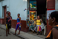 HAVANA, CUBA - SEPTEMBER 08: Cuban stand in front of a store with Cuban art for sale in Old Havana on 8th of September, 2015 in Havana, Cuba. <br /> <br /> Daniel Berehulak for The New York Times