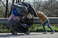 Pictured: A male migrant, carrying all his belongings in a pushchair, walks on the motorway to get to Idomeni, Greece Wednesday 02 March 2016<br /> Re: More migrants have been arriving at the Greek FYRO Macedonian border of Idomeni, Greece.