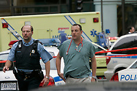 A policeman and an paramedic at the scene of a school shooting in Montreal Dawson College. Carrying an automatic rifle, two other guns, and dressed head to toe in black, the man stormed into the sprawling downtown Dawson College and began coldly cutting down students. Ninteen people were wounded, five critically, One dead.<br /> <br /> Several published reports identified the gunman as Kimveer Gill, 25, of Laval, north of Montreal. Police would not confirm the gunman's identity. <br /> Photo byYves Provencher/ Images Distribution