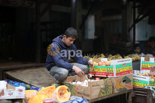 A Palestinian boy sells vegetables at the market in Shati refugee camp in Gaza city on Jan. 07, 2016. Photo by Ezz al-Zanoun
