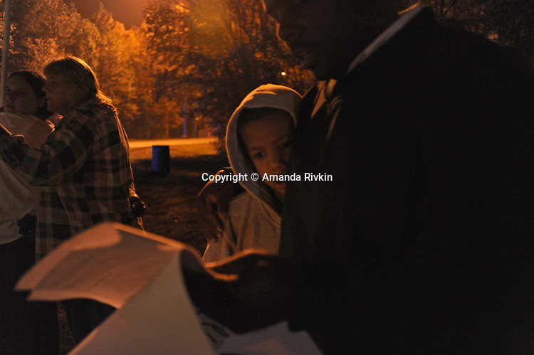 "Desmond Lane, 11, with his father, Darick Lane, 38, of Richmond, Virginia, opponents of the death penalty, read a prayer together during a prayer vigil near the entrance to the Greensville Correctional Center hours before the 9 p.m. execution of John Allen Muhammad, the so-called ""Washington sniper"" responsible for gunning down 10 and wounding three in the D.C.-area in 2002, on November 10, 2009.  Virginia Governor Tim Kaine refused to grant a stay of clemency and the U.S. Supreme Court turned down the request for a stay of execution despite religious objections due to Muhammad's mental health."