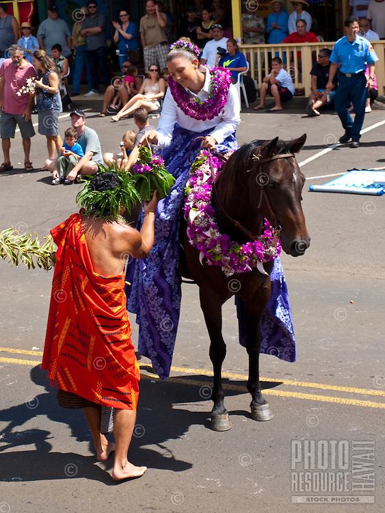 Hula dancer passing a ho'okupu gift to a Pa'u rider on horseback in King Kamehameha Day Parade, North Kohala, Big Island of Hawaii, Kapa'au Town.