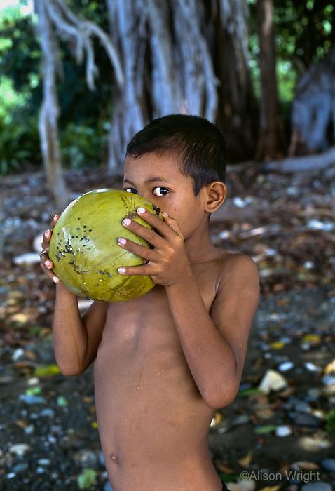 Boy drinking coconut on Wetbar island, Indonesia, 2005