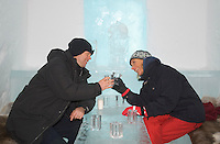 Sweden, SWE, Kiruna, 2006-Apr-12: A woman and a man clinking glasses made of ice in the icebar of the Jukkasjarvi icehotel.