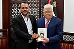 Palestinian President Mahmoud Abbas recives the complete works poetry of Ahmed Dahbour at his headquarters in the West Bank city of Ramallah on March 2, 2018. Photo by Osama Falah