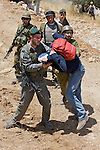 An IDF soldier wrestles with an activist who resisted arrest while other soldiers look on at a construction site for Israel's controversial West Bank barrier in Beit Jala, near Bethlehem, on Sunday May 23th 2010. Palestinian, Israeli & International activists held up construction work for a short period of time with a non violent demonstration.
