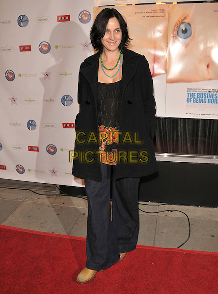 "CARRIE ANN MOSS.attends ""The Business of Being Born"" L.A. Premiere held at The Fine Arts Theatre in Beverly Hills, California, USA, January 14th 2008..full length black coat jacket anne green turquoise neacklaces wide leg jeans   .CAP/DVS.©Debbie VanStory/Capital Pictures"