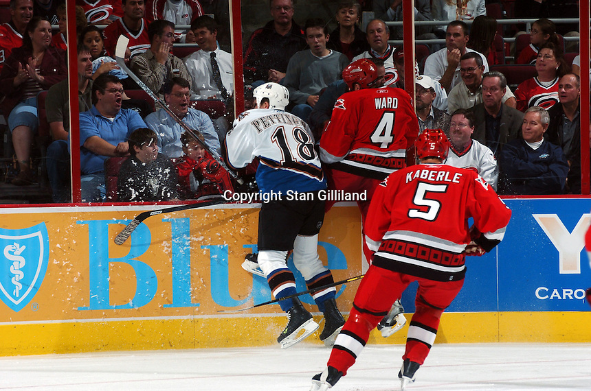 Carolina Hurricanes' Aaron Ward (4) and Washington Capitals' Matt Pettinger (18) slam into the boards as Frantisek Kaberle (5) of the Czech Republic watches during their game Wednesday, Oct. 12, 2005 in Raleigh, NC. Carolina won 7-2.