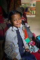 Binita Tamang (10) poses for a portrait in her school uniform in her temporary shelter in Kavre, Bagmati, Nepal on 30 June 2015.  Her mother, Kalpana, a widow with 3 children, has been supported by SOS Children's Villages for many years now and had receive the Home-in-a-Box after the earthquake destroyed her house, almost killing her two daughters. She now lives in a temporary shelter, sharing her dwelling with farm animals, and is trying to make ends meet by weaving bamboo baskets to supplement the financial assistance provided by SOS Childrens Villages. The NGO mostly supports her children's welfare and schooling as well as provides her with essential household and schooling items like kitchen utensils and school books and uniforms. Photo by Suzanne Lee for SOS Children's Villages