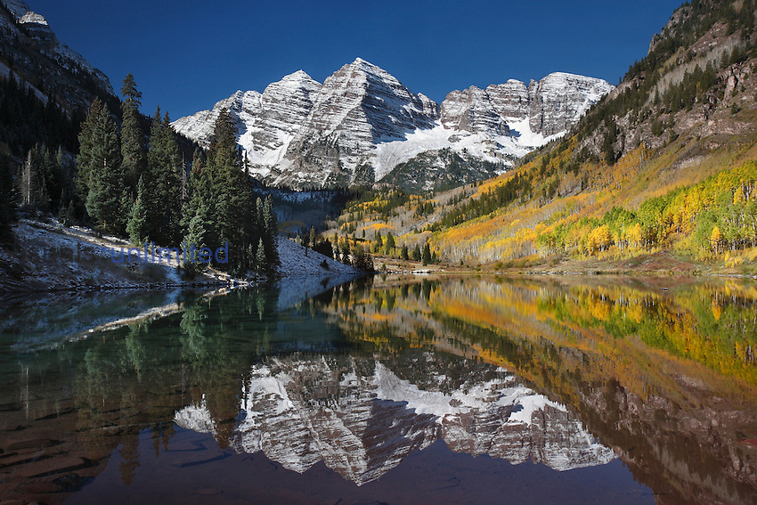 Fresh snowfall on Maroon Bells at over 14,000 ft reflects in Maroon Lake, Colorado, USA.