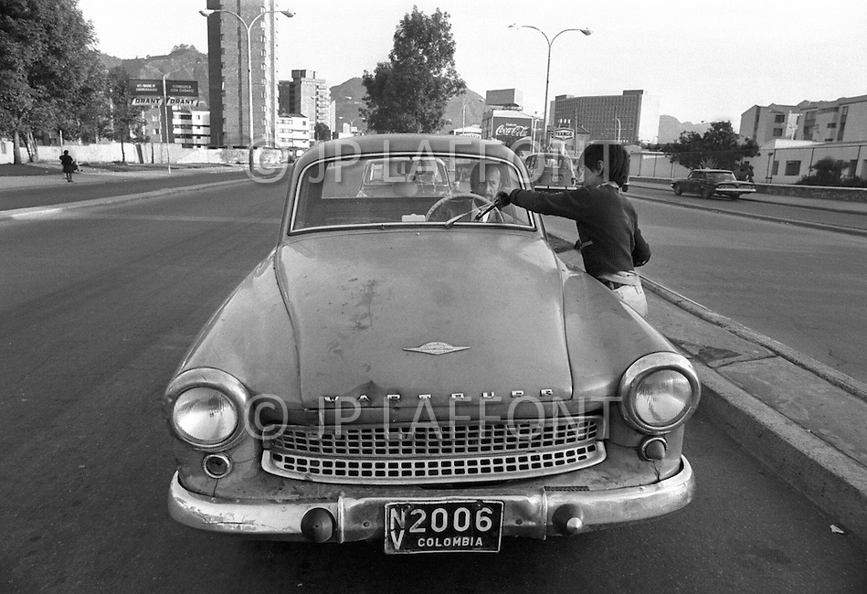 Childen clean car windows and beg for money in Bogota, Colombia - Child labor as seen around the world between 1979 and 1980 – Photographer Jean Pierre Laffont, touched by the suffering of child workers, chronicled their plight in 12 countries over the course of one year.  Laffont was awarded The World Press Award and Madeline Ross Award among many others for his work.