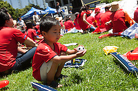 Los Angeles, CA -  Sunday, June 22, 2014: A young Korean fan plays with a miniature soccer ball as Koreans watch the South Korea vs. Algeria first round match on the  front lawn of Wilshire Park Place.