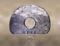 "Bronze Age Hattian ceremonial standard known as ""Sun Disks"" in silver from a possible Bronze Age Royal grave (2500 BC to 2250 BC) - Alacahoyuk - Museum of Anatolian Civilisations, Ankara, Turkey. Against a warm art background"