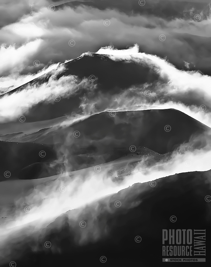 Morning clouds roll over Mt. Haleakala in Haleakala National Park, Maui. Numerous sliversword plants endemic to Haleakala look like small lights dotting the landscape. This image won 1st Place B&W - State Open at the 1998 Maui County Fair's photo contest.