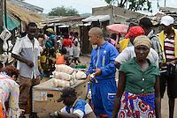 MOZAMBIQUE, Moatize, chinese worker goes shopping at street market / MOSAMBIK, Moatize, chinesischer Arbeiter auf einem Markt an der Strasse
